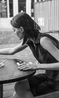 Light-Zigaretten - junge Raucherin am Tisch